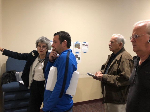 Commissioner Cook explains landscaping plans posted on the Church walls of trees and plants for Neenah Ave. to Davis Spring residents Nick Mock, Brig Mireles and Ron Meredith.