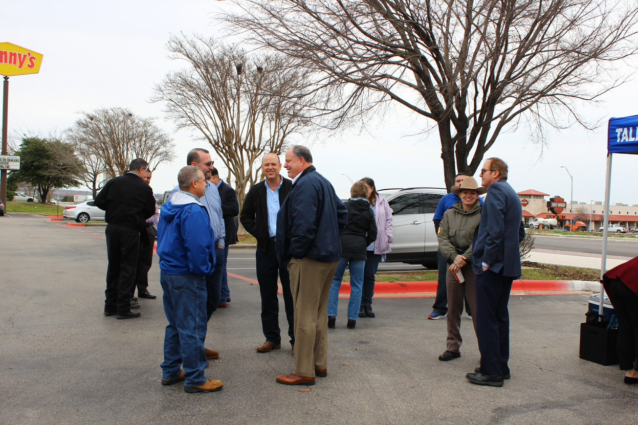 Local and elected leaders visit with TxDOT representatives before the ribbon cutting ceremony outside.